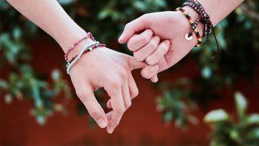 【手荒れの原因って?】 種類ごとの特徴や原因 3つの効果的な対策も紹介、という記事中のイメージ画像です。緑葉を背景に2人の手が小指をつないでいます。